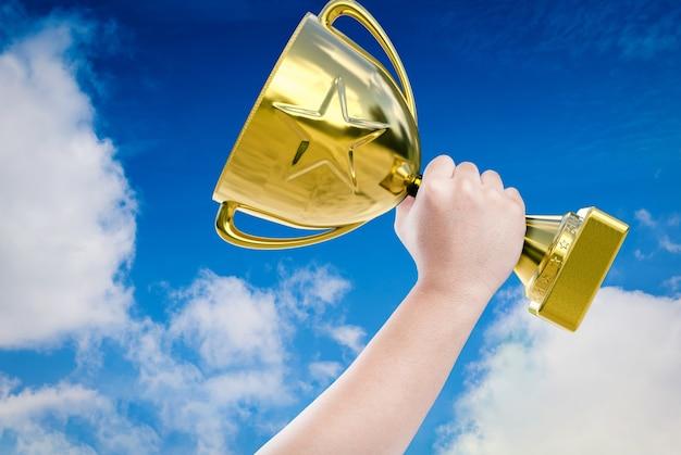 Hand met gouden trofee met blauwe hemelachtergrond
