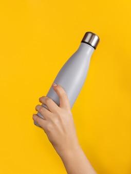 Hand met grijze herbruikbare geïsoleerde fles op geel