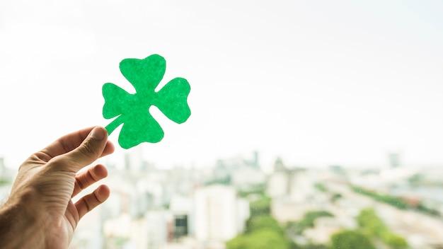 Hand met groenboek klaver en uitzicht op stadsbeeld