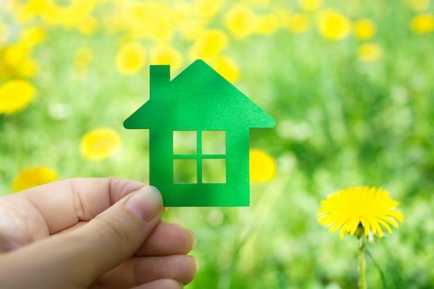Hand met groene eco huisje in de natuur