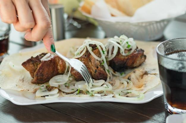 Hand met groene nagels neemt het vlees met een vork.