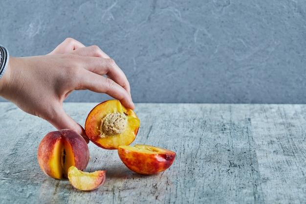 Hand met halve perzik gesneden op marmeren oppervlak