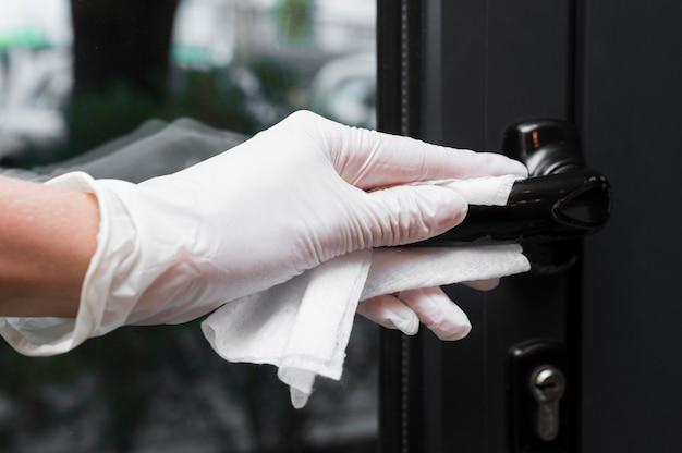Hand met handschoen die deurgreep desinfecteert
