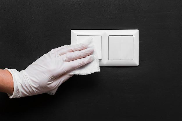 Hand met handschoen die lichtschakelaars desinfecteert