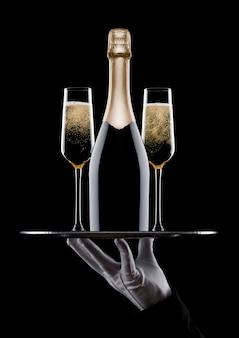 Hand met handschoen houdt dienblad met champagneglazen