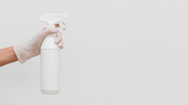 Hand met handschoen met reinigingsoplossing in fles met kopie ruimte