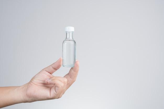 Hand met helder smeersel of gebruik van kruidenolie voor massage om spieren, pezen, gewrichten te verlichten