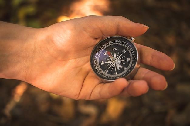 Hand met het kompas in bos, openluchtnavigatieconcept achtergrondfoto