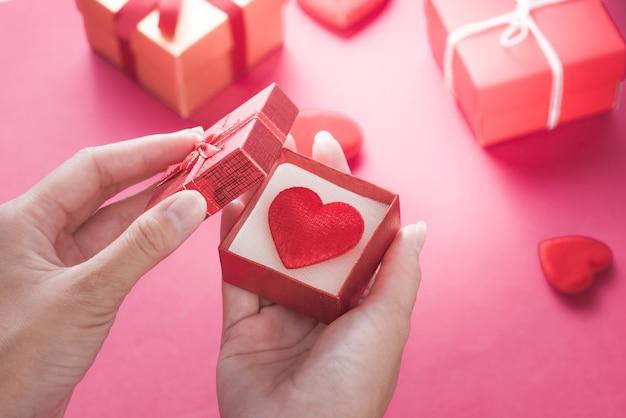 Hand met het openen van een geschenkdoos met rood hart voor liefde bruiloft of valentijnsdag.