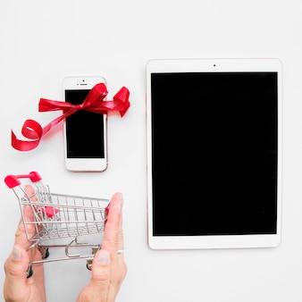 Hand met het winkelen karretje dichtbij tablet en smartphone