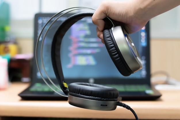 Hand met hoofdtelefoon op laptop achtergrond.