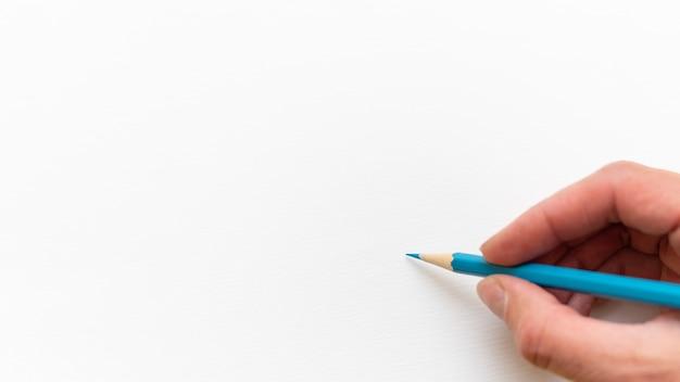 Hand met houten blauw scherp eenvoudig potlood voor tekenen of schetsen op witte blanco bladachtergrond, close-up, kopieer ruimte. terug naar schoolconcept.