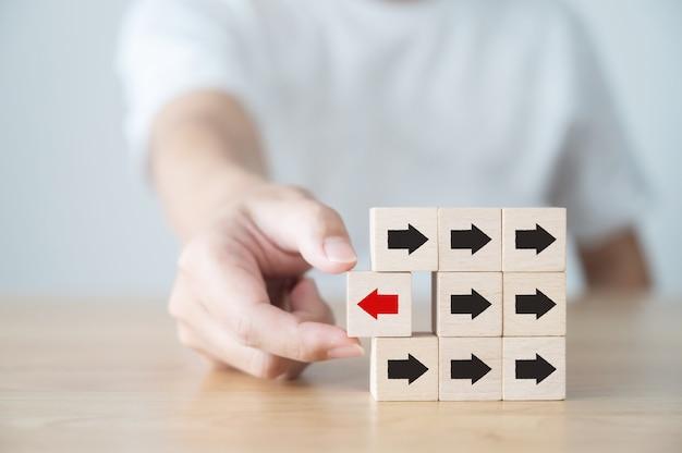 Hand met houten blok met rode pijl in de tegenovergestelde richting zwarte pijlen, uniek, denk anders, individueel en onderscheidend van het concept van de menigte