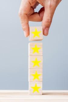 Hand met houten blokken met het stersymbool. klantrecensies, feedback, beoordeling, rangschikking en serviceconcept.
