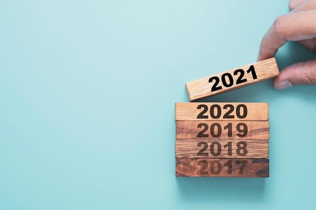 Hand met houten blokkubus die het scherm 2021 jaar afdrukt en boven het jaar 2020 met blauwe achtergrond neerzet.