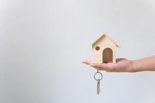Hand met houten huis en huis sleutelhanger. investeringen in onroerend goed en financieel onroerend goed van een hypotheek