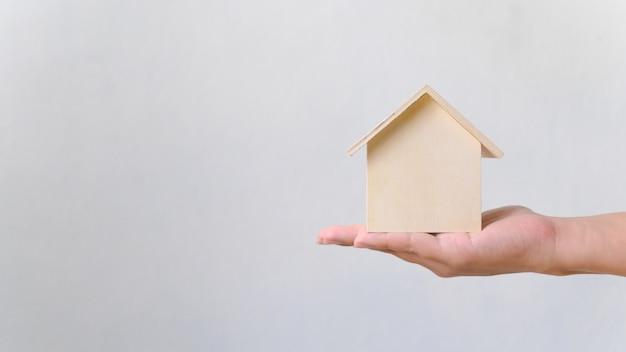 Hand met houten huis. onroerend goed investeringen en huis hypotheek financieel onroerend goed concept