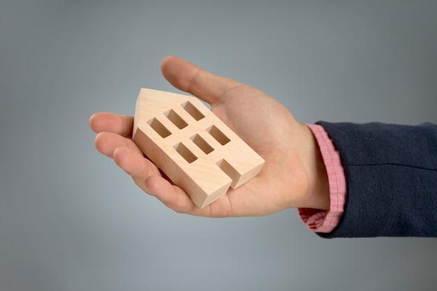 Hand met houten huis