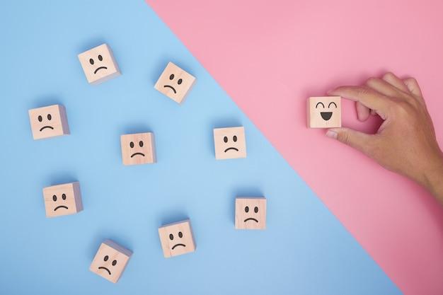 Hand met houten kubus met smiley gezicht pictogram symbool op blauwe en roze achtergrond. klantenservice rating, tevredenheidsonderzoek concept.