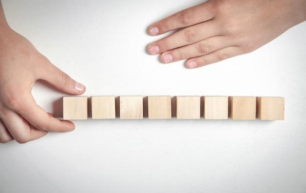 Hand met houten kubus op een wit bureau.