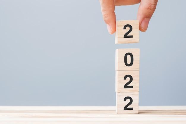 Hand met houten kubusblok met 2022 tekst op tabelachtergrond. resolutie, plan, beoordeling, doel, start en nieuwjaarsvakantieconcepten