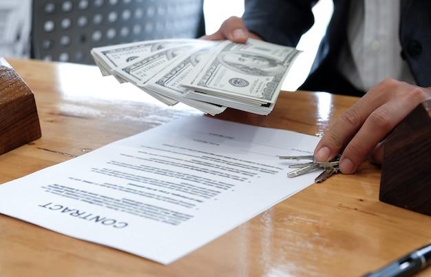 Hand met huissleutel en dollars met overeenkomst document en model huizen.