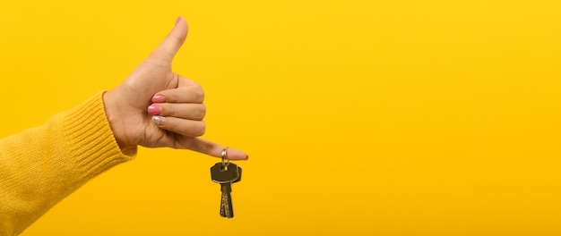Hand met huissleutels over gele ruimte