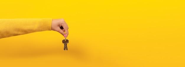 Hand met huissleutels, suggererend, over gele ruimte