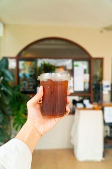 Hand met ijskoude americano-koffie in afhaalglas