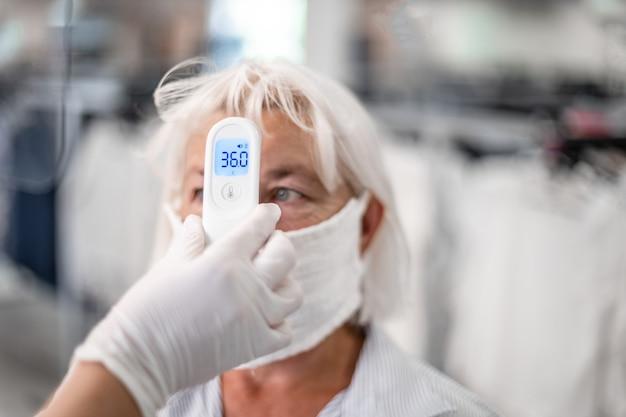 Hand met infrarood thermometer voor het meten van temperatuur vrouw met gezichtsmasker