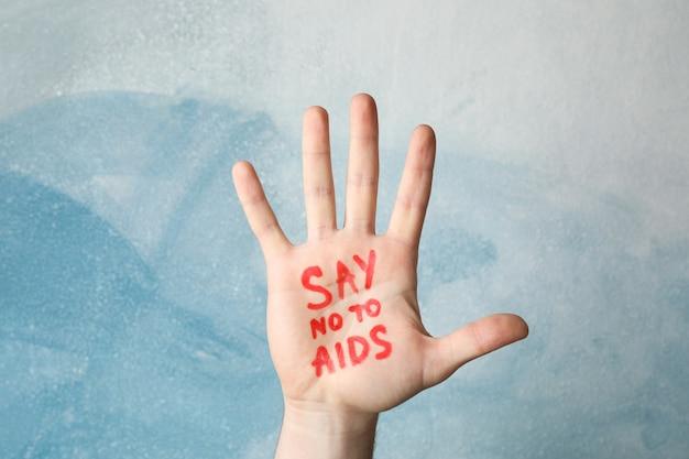 Hand met inscriptie zeg nee tegen aids op blauwe muur, kopieer ruimte