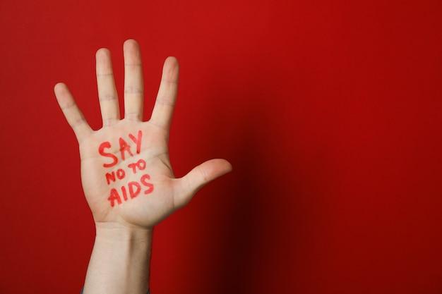 Hand met inscriptie zeg nee tegen aids op rode muur, kopieer ruimte