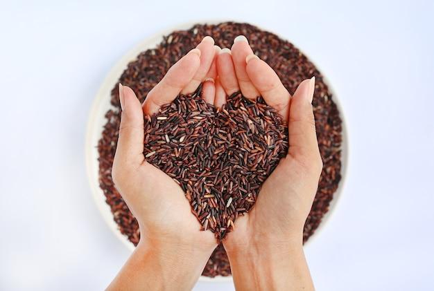 Hand met jasmijn rode rijst in vorm van liefde op witte plaat tegen een witte achtergrond