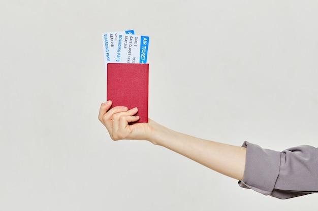 Hand met kaartjes en paspoort.