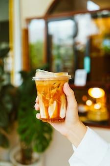 Hand met karamel macchiato-koffie in afhaalglas