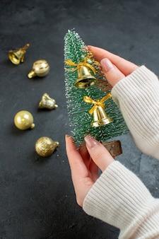 Hand met kerstboom en decoratie accessoires op donkere achtergrond