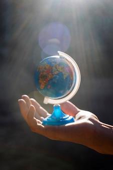 Hand met kleine wereldbol