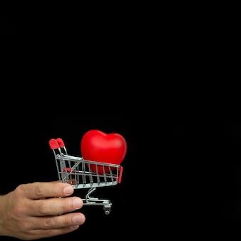 Hand met kleine winkelwagen en rood hart op donkere achtergrond
