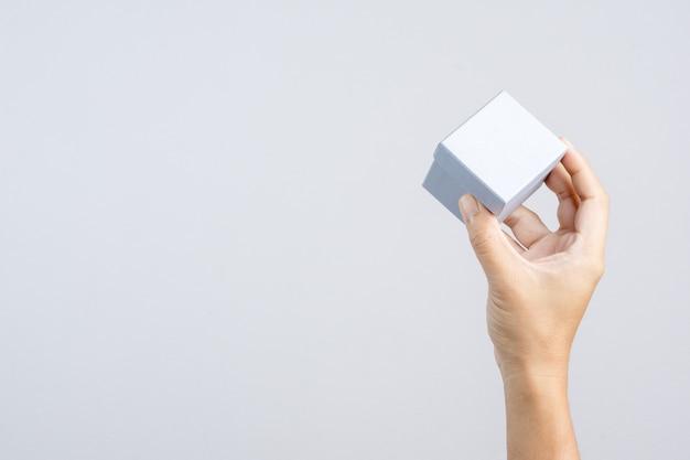 Hand met kleine zilveren luxe geschenkdoos voor speciale gelegenheid