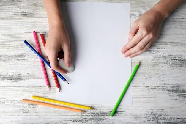 Hand met kleurpotloden en blanco vel papier op houten tafel