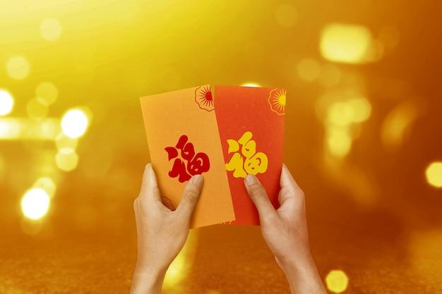 Hand met kleurrijke enveloppen (angpao) met wazig lichte muur. gelukkig chinees nieuwjaar