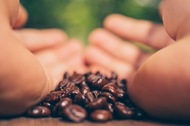 Hand met koffie koffieboon op houten tafel