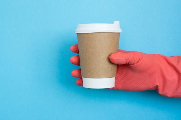 Hand met koffie papieren beker, coronavirus bescherming.