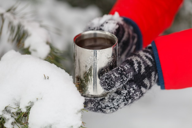 Hand met koffiekopje, buitenshuis