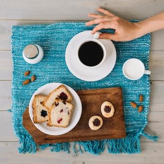 Hand met koffiekopje in de buurt van plaat met taart
