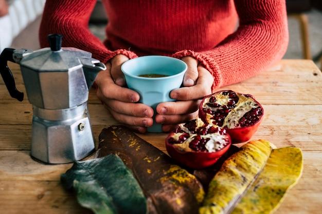 Hand met koffiekopje met gehalveerde granaatappel op tafel in restaurant. close up van handen met een warme koffiekopje met vers fruit op houten tafel tijdens het ontbijt in café.