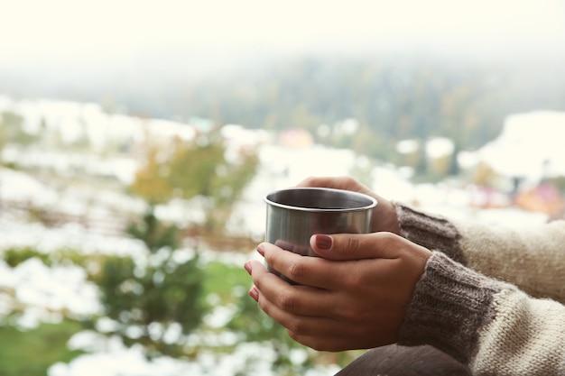 Hand met koffiekopje op bergen