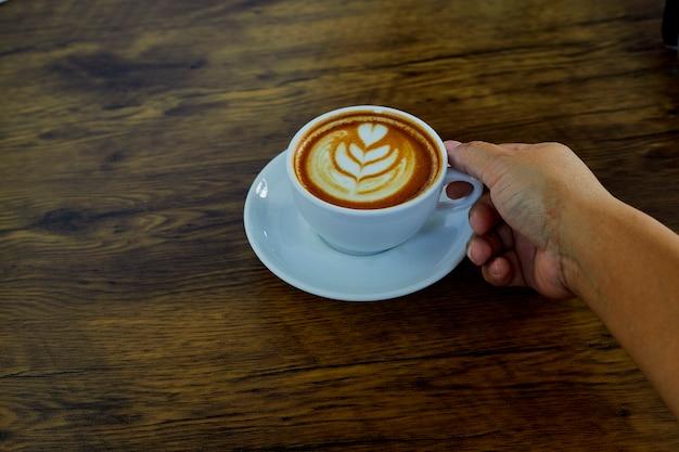 Hand met koffiekopje op tafel