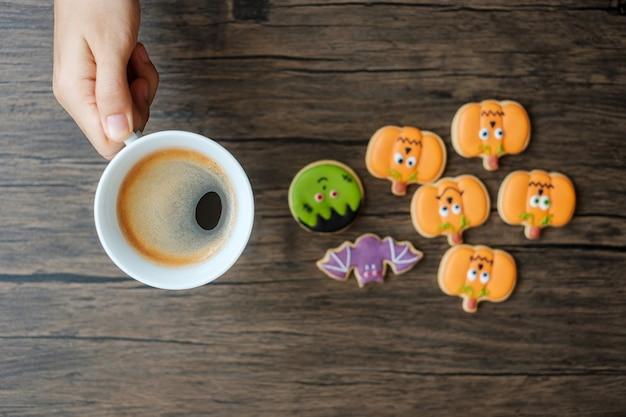 Hand met koffiekopje tijdens het eten van grappige halloween cookies. fijne halloween-dag, trick or threat, hallo oktober, herfstherfst, traditioneel, feest- en vakantieconcept