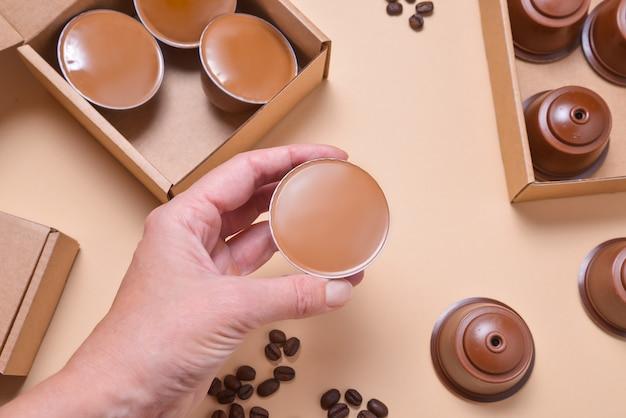 Hand met koffiemachine peulen, capsules op beuge achtergrond